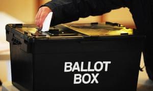 a man cast his vote into a black ballot box