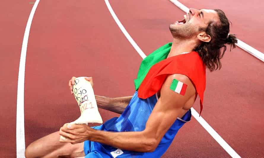 Italy's Gianmarco Tamberi holds his cast as he celebrates following the men's high jump final at the Tokyo 2020 Olympic Games