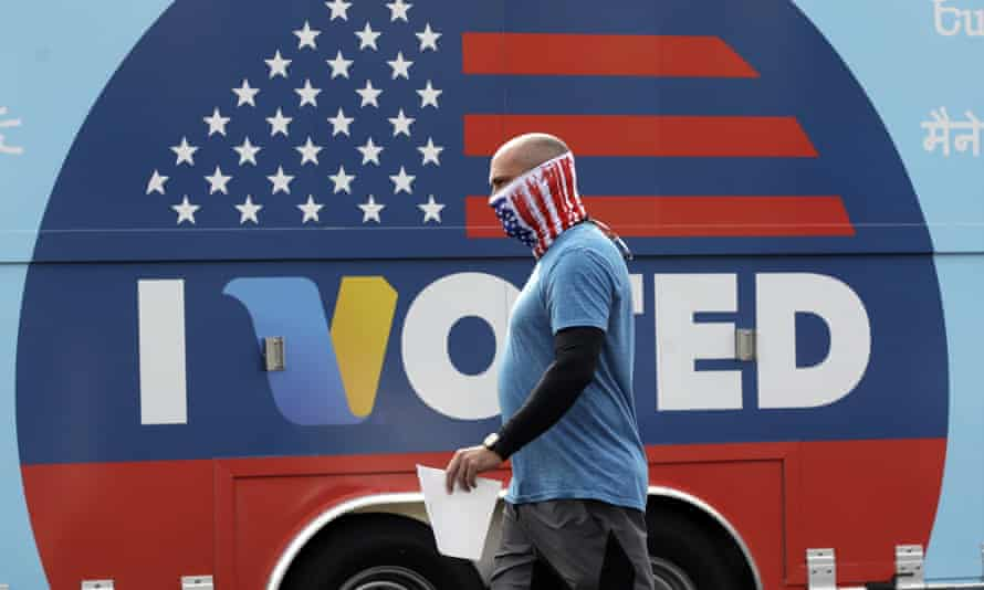 A man wears a mask as he walks to cast his vote.