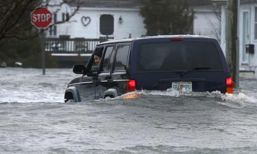 The driver of an SUV looks out of his window on a flooded 10th Ave. in North Wildwood, N.J., at the height of the storm, later backing down the street, Saturday, Jan. 23, 2016. A winter storm created near record high tides along the Jersey Shore, surpassing the tide of Hurricane Sandy according to North Wildwood city officials. (Dale Gerhard/Press of Atlantic City via AP)
