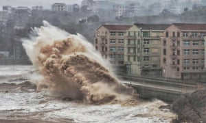 High waves break against a sea wall in front of buildings in Taizhou, China