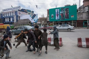 A street in Kabul with a billboard advertising soft drinks in the background.