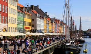 View of the Nyhavn area of Copenhagen with multi-coloured buildings, the canopies of restaurants lining the canal and crowds of people