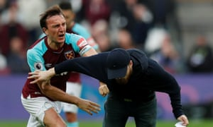 West Ham United's Mark Noble clashes with a fan who has invaded the pitch in their defeat to Burnley.