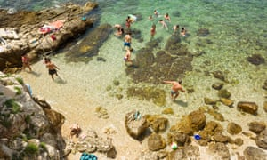 A high angle view of people swimming in the shoal and sunbathing on the rocks of the city beach in Rovinj, Croatia