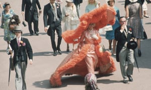Woman walking along at the Ascot races in 1969 wearing a dress with a hoop and an enormous hat with feathers