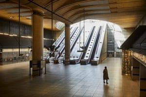 The bank of escalators at the cathedral-like Canary Wharf move passenger-less to the outside.