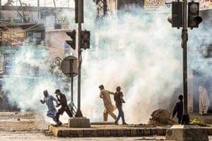 Supporters of Tehreek-e-Labbaik Pakistan party disperse after police fired teargas during a protest against the arrest of their leader