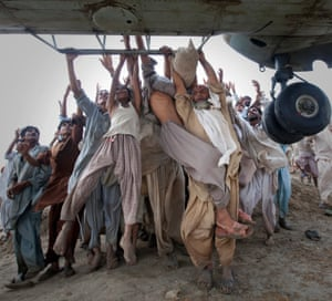 Marooned flood victims looking to escape grab the side bars of a hovering Army helicopter which arrived to distribute food supplies in the Muzaffargarh district of Pakistan's Punjab province. The disaster killed more than 1,600 people and disrupted the lives of 12 million. 7 August, 2010