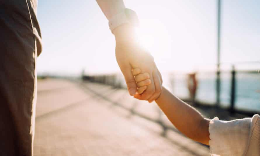 Close-up of young mother walking hand in hand with her daughter