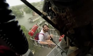 A woman is rescued from flood waters by a US navy helicopter crew in Beaumont.