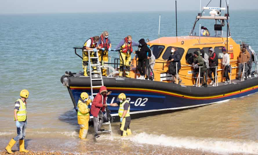 """An RNLI lifeboat helps migrants ashore on Dungeness beach, Kent, as onlookers shout """"traitor"""" at the crew."""