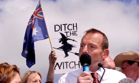 Tony Abbott standing in front of a placard reading 'Ditch the witch'.