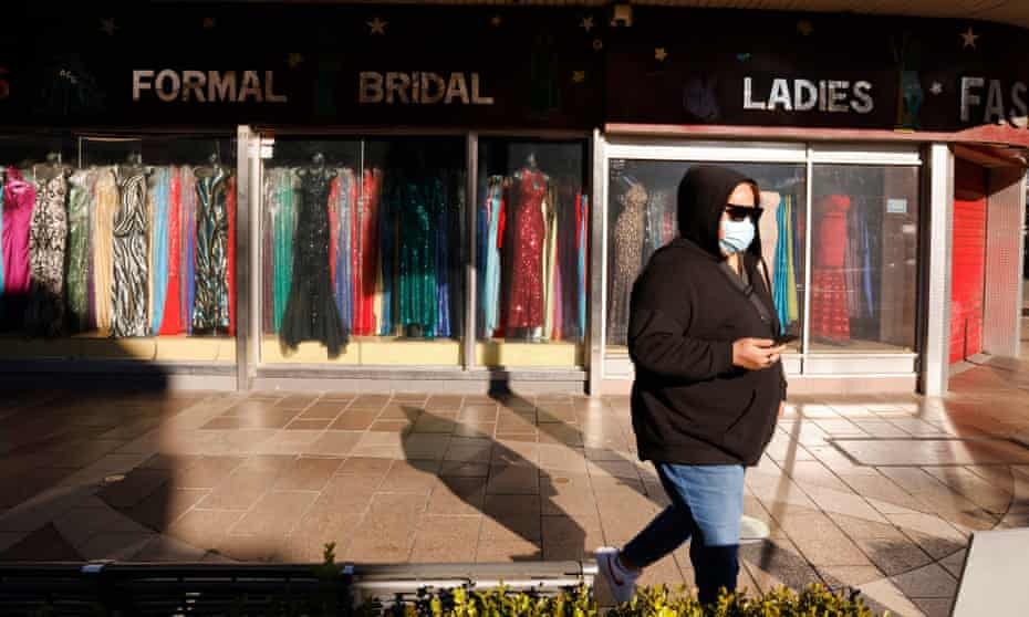 A woman is seen outside a closed clothing store in Fairfield in Sydney earlier this month.