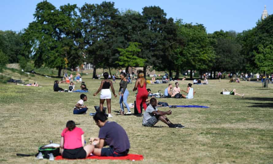 People enjoy the weather in a London park.