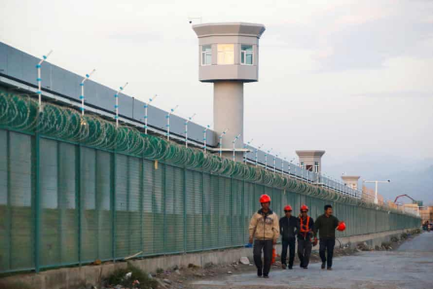 Workers walk by the perimeter fence of what is officially known as a vocational skills education center in Xinjiang Uyghur autonomous region in China on 4 September 2018.