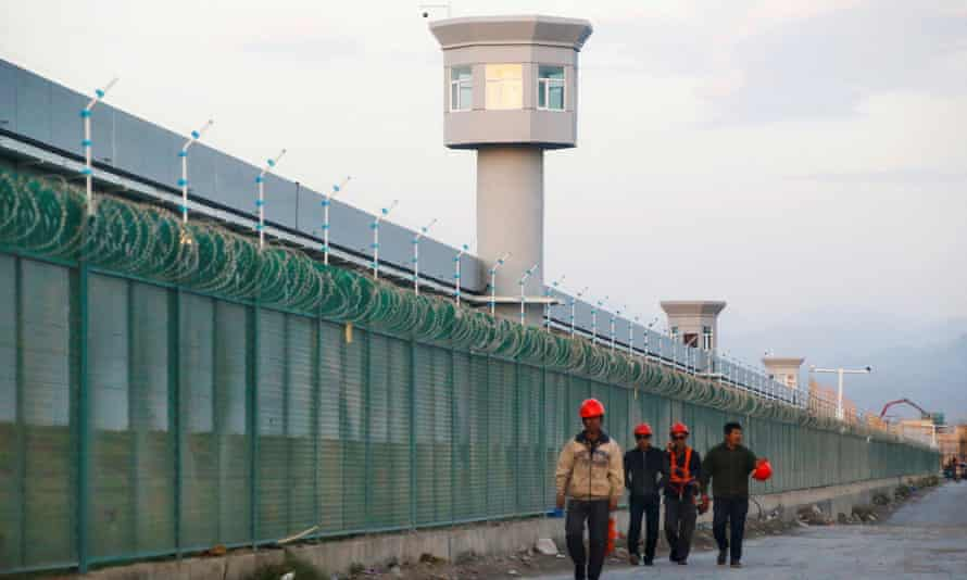 Workers walk by the perimeter fence of what is officially known as a vocational skills education centre in Dabancheng, Xinjiang, China.