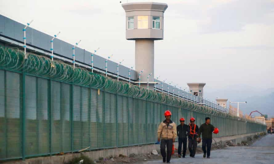 Workers walk by the perimeter fence of what is officially known as a Uighur 'vocational skills education centre' in Dabancheng, Xinjiang, China.