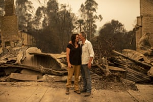 Business owner Sally Anne Wilson (left) stands in front of her destroyed shop with her partner Christopher Lee in Cobargo, NSW, Wednesday, January 1, 2020.