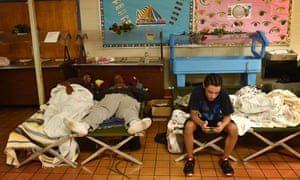 Flood-displaced residents rest at a temporary shelter at St Andrews middle school in Columbia, South Carolina.