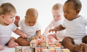 Four babies in white vests sitting on floor playing with blocks