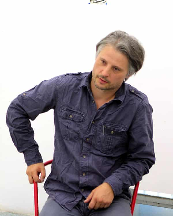 Sebastian Bieniek in a blue shirt and jeans, sitting on a director's chair
