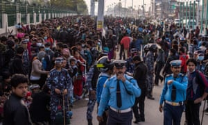 People queue on the street outside a government building as they wait for free bus rides out of Kathmandu.