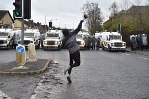 A man throws a missile at police