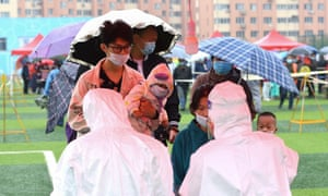 People line up in the rain to be tested for the Covid-19 coronavirus as part of a mass testing programme following a new outbreak in Qingdao in China's eastern Shandong province on 14 October 2020.