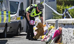 A police officer lays flowers on behalf of a member of the public outside Alesha's grandparents' house.