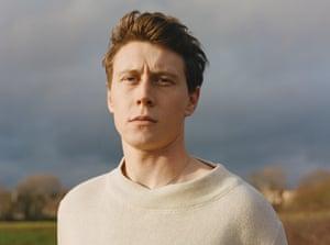 Headshot of George MacKay, against grey sky and field backdrop, January 2020
