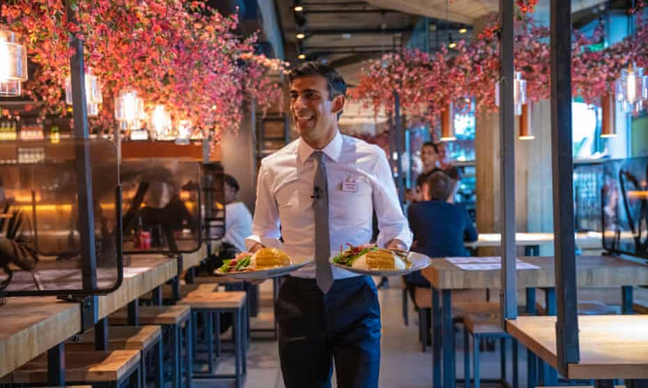 Sunak in a shirt and tie, with a name badge, carrying two plates of food to a table in an illuminated outdoor dining area.