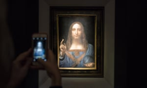A visitor takes a photo of Salvator Mundi