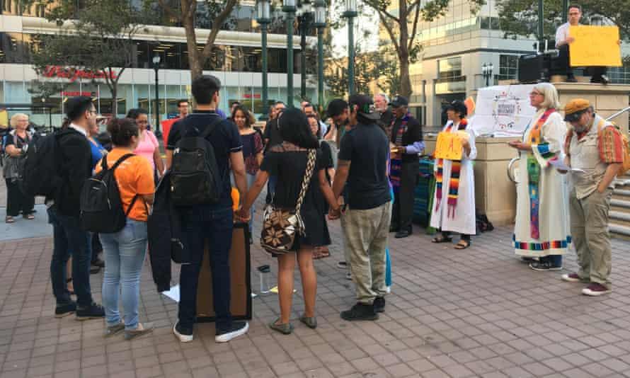 Daca recipients hold hands at a vigil in Oakland.