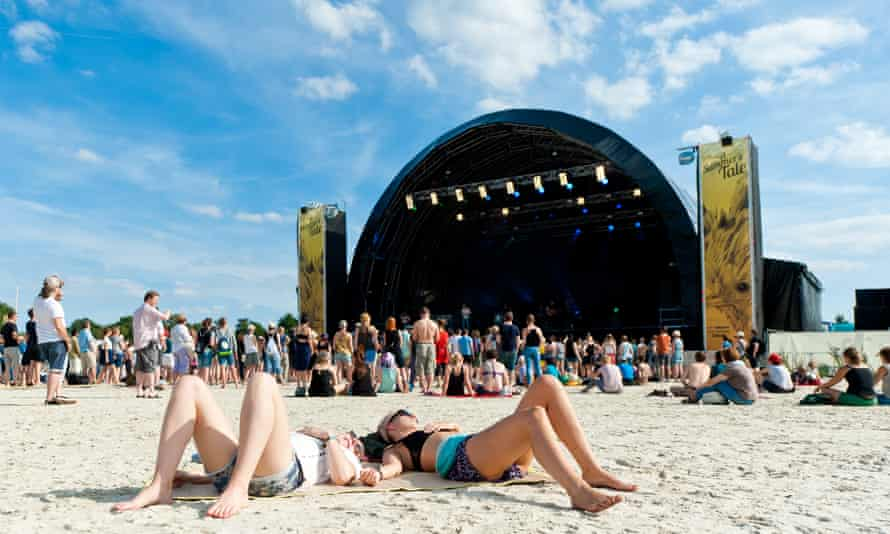 Revellers lie on the sand in front of a festival music stage at A Summer's Tale, Germany