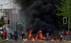 Demonstrators stand next to a burning barricade in Chile