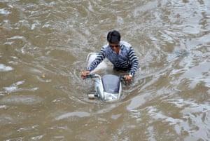 Mathura, India: A man wades through a flooded street after heavy rainfall