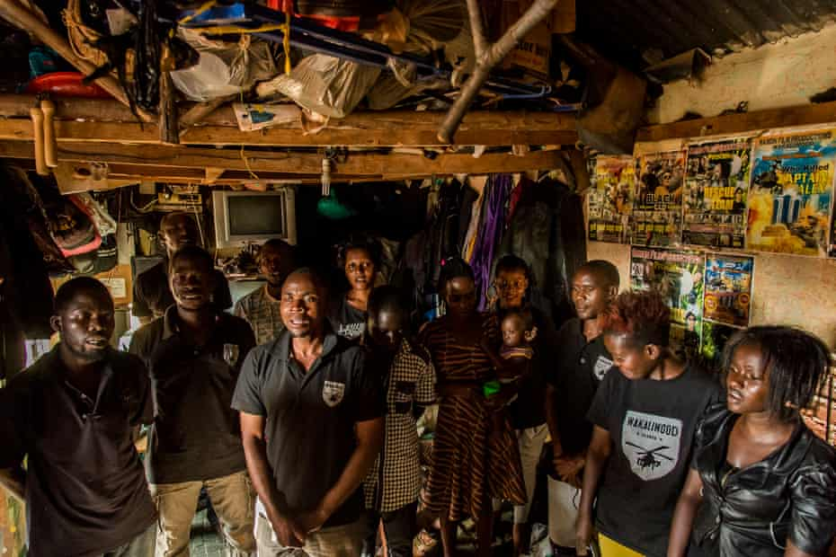 Wakaliwood's actors sing the anthem of Ramon Studio following every day of work or shooting, in the rehearsing and stocking room.