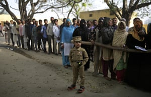 In a village near Meerut, Uttar Pradesh, a young boy dressed as a policeman stands in front of people waiting to cast their votes. With the country's population estimated at 1.3 billion, the general election is the world's largest to date.