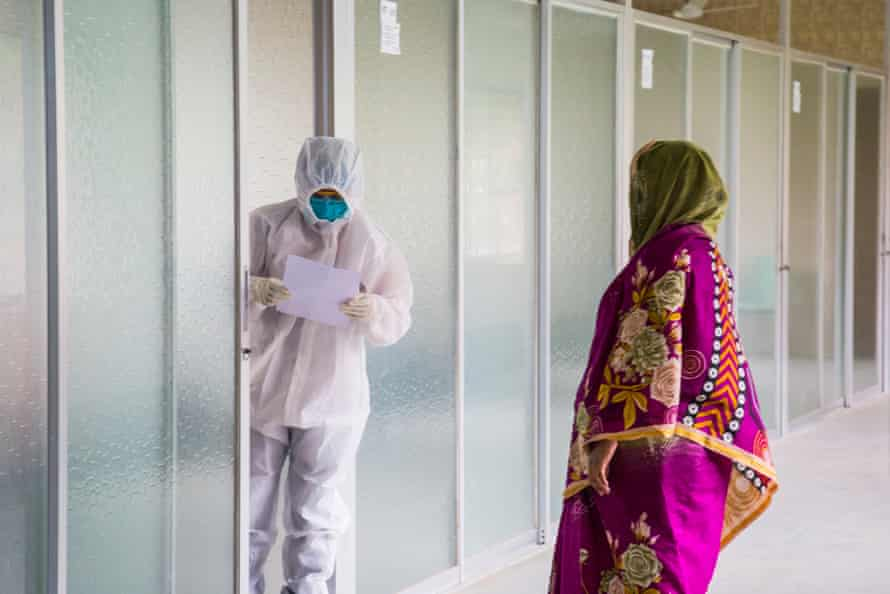 A woman with suspected coronavirus gives her data to a health worker in a white protective suit at a collection point