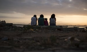 Girls sit near the shores of Guanabara Bay, the venue for sailing at Rio 2016.
