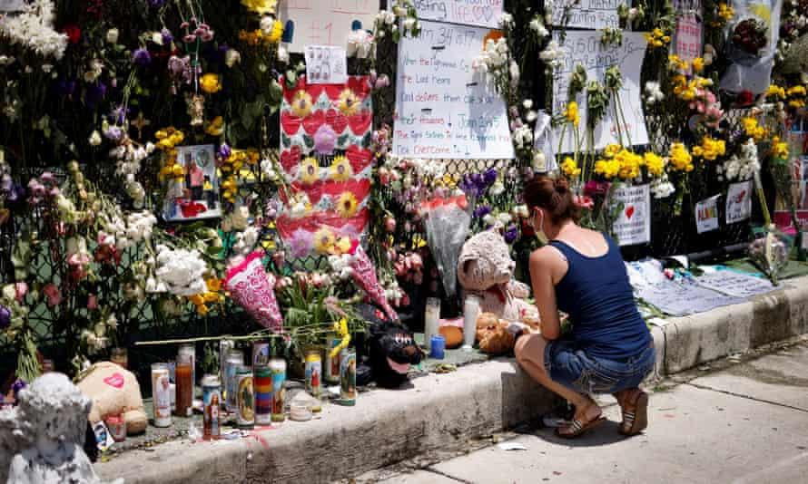 woman kneels at memorial site created by neighbors in Surfside, Florida.