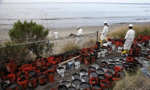Plastic buckets with oil collected from the beach are placed at the side at Refugio state beach.