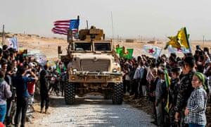 Syrian Kurds gather round a US armoured vehicle