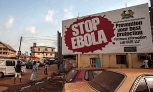 People pass a banner reading 'Stop Ebola' forming part of Sierra Leone's Ebola free campaign in the city of Freetown, Sierra Leone.
