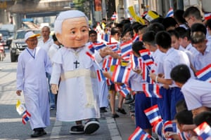 A man dressed as Pope Francis greets young students waving Thai and Vatican flags