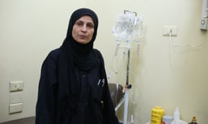 Syrian female medic, Umm Abdu, stands in front of medical equipment