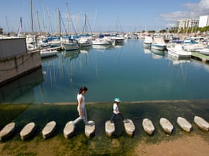 A mother and son walk at the Portixol yacht club in Palma de Mallorca