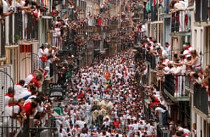 Participants run in front of bulls and steers during the first running of the bulls at the San Fermin festival in Pamplona, Spain.