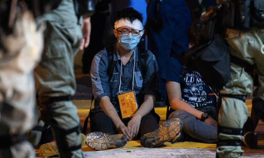 Detained and injured protesters wait to be evacuated by ambulance near Polytechnic University of Hong Kong in 2019.